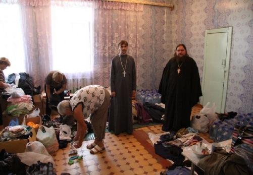 Иерей Константин Зубарев и иерей Георгий Борисов (слева направо) привезли предметы первой необходимости в центр временного размещения в селе Бабстово