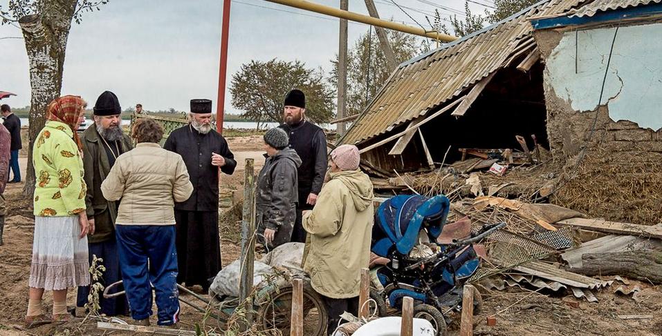 Епископ Герман (второй слева) и сотрудники епархиальной комиссии беседуют с жителями пострадашего поселка
