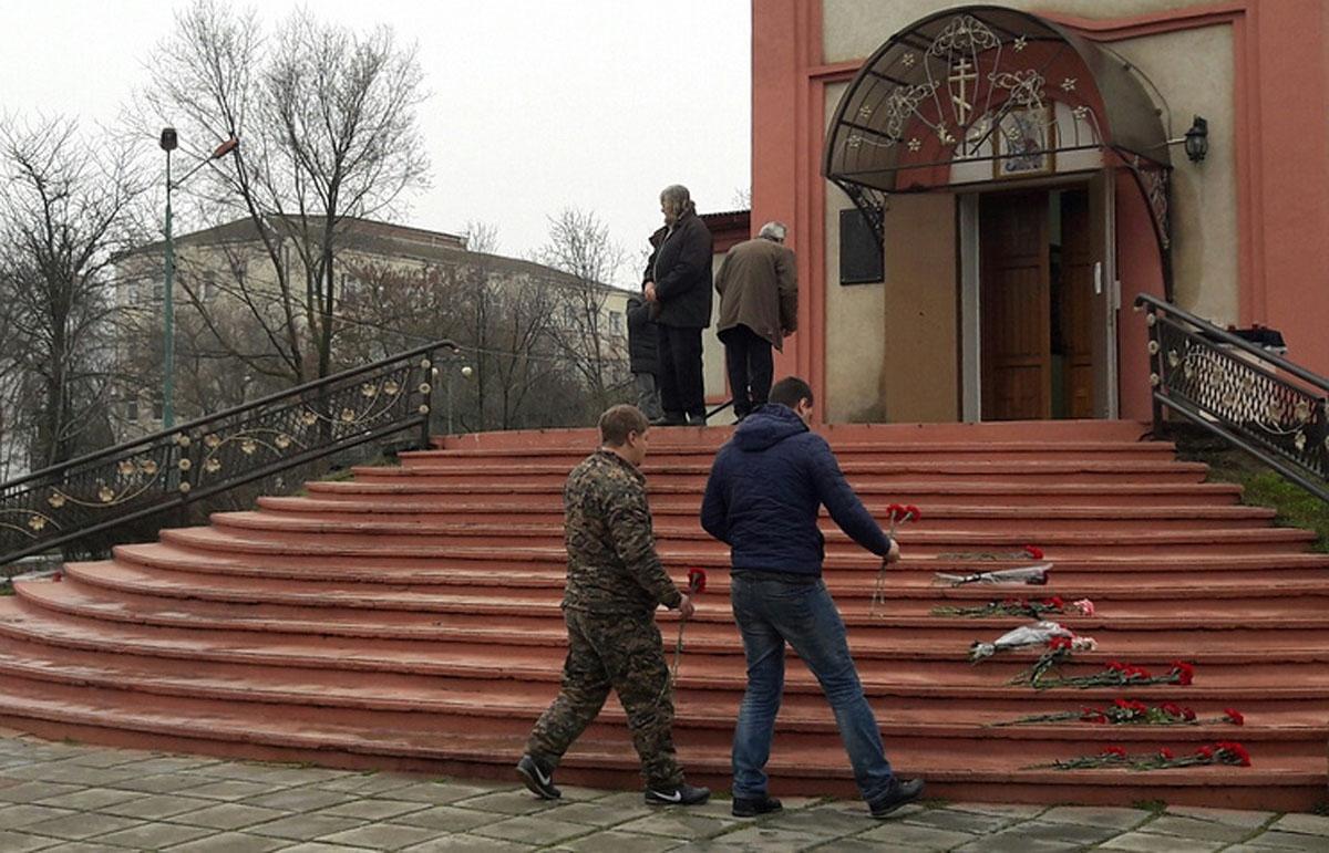 Люди возлагают цветы к храму Георгия Победоносца в Кизляре. Фото: Низами Гаджибалаев/ТАСС