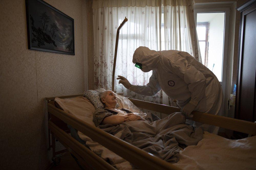 Священник из специальной группы Больничной Комиссии Московской епархии у постели больной. Фото: AP