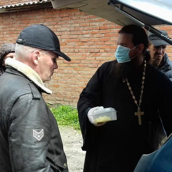 Священник Иоанн Усачев выдает готовую еду для бездомных возле томского городского Центра социальной адаптации