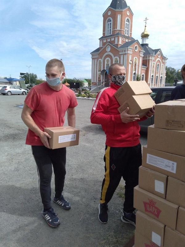 Добровольцы разгружают продовольственную помощь в Курганской епархии