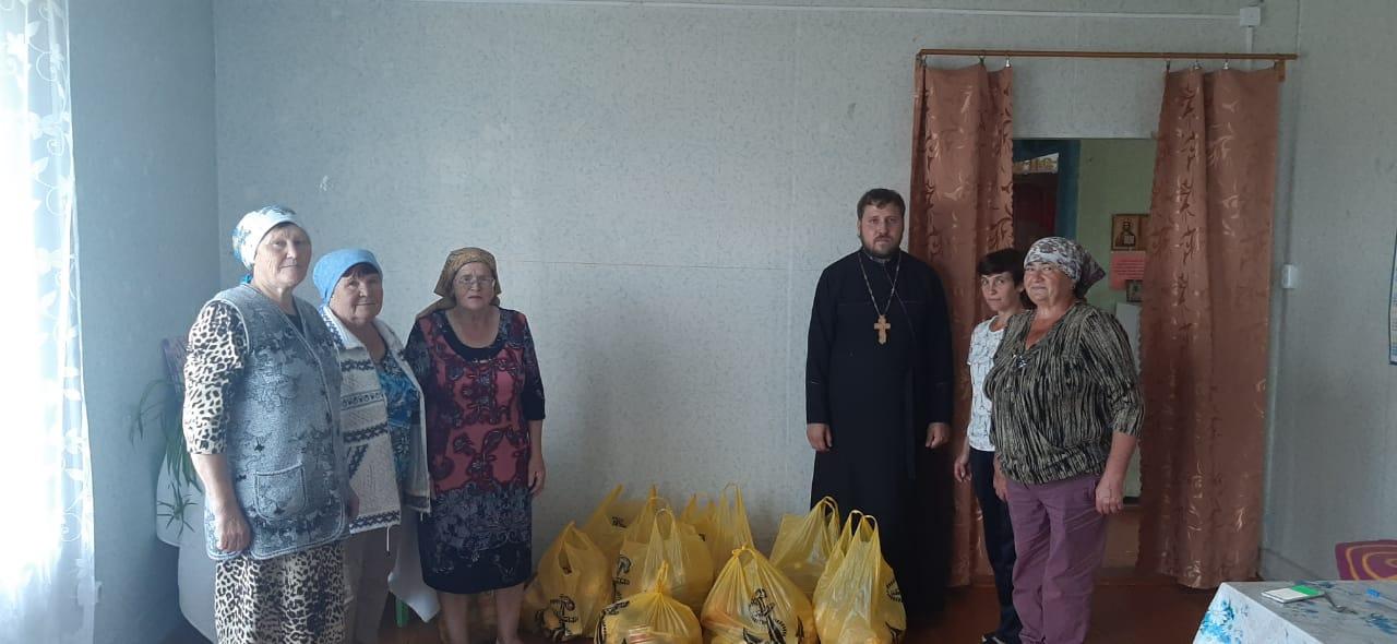 Рководитель социального отдела Братской епархии иерей Николай Осипов и пожилые, получившие продуктовую помощь
