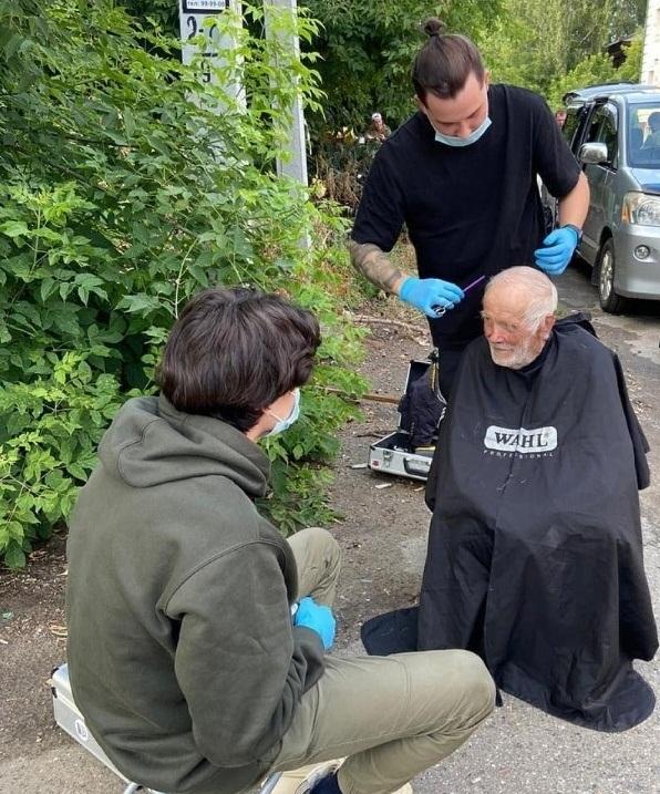 Сотрудник одного из барбершопов Томска постригает бездомного