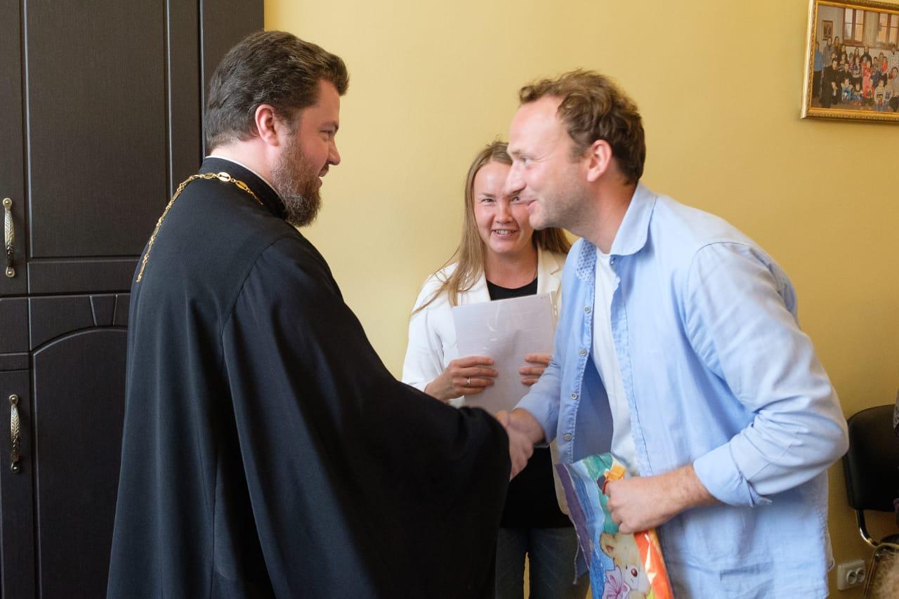 Руководитель православной школы приемных родителей «Умиление» иерей Феодосий Амбарцумов вручает свидетельство об окончании школы выпускнику четвертого потока