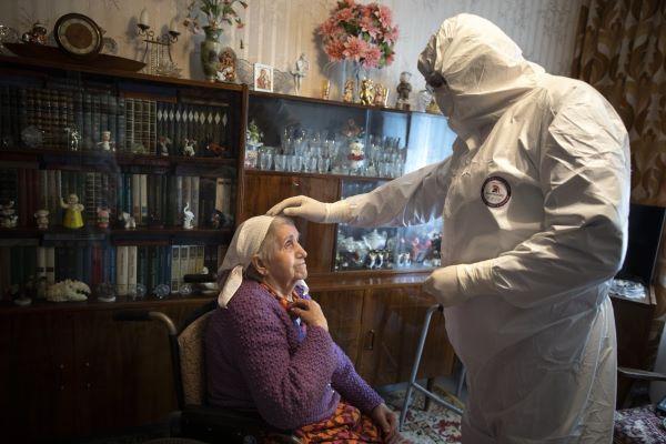 Священник из специальной группы Больничной Комиссии Московской епархии во время посещения прихожанки на дому. Фото: AP, Александр Земляниченко