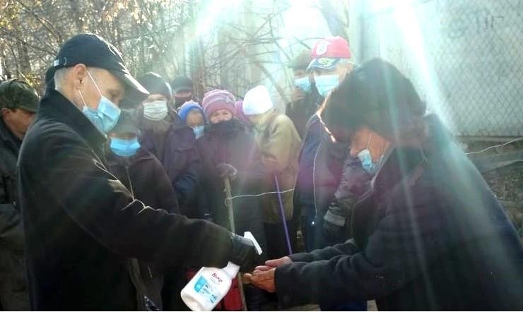 Дезинфекция рук перед раздачей православными добровольцами горячих обедов нуждающимся в Чебоксарах