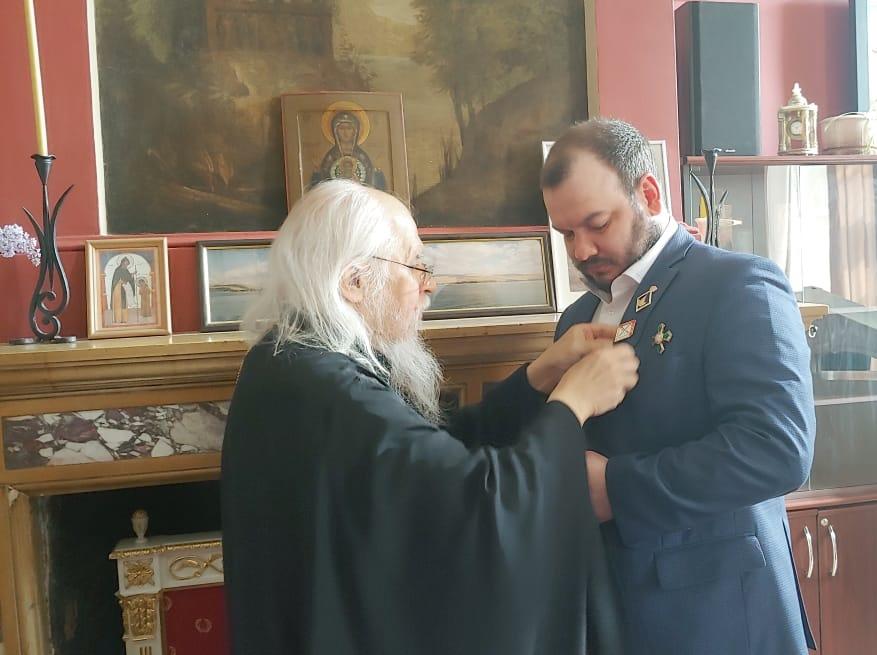Председатель Синодального отдела по благотворительности епископ Верейский Пантелеимон вручает награду Илье Кускову