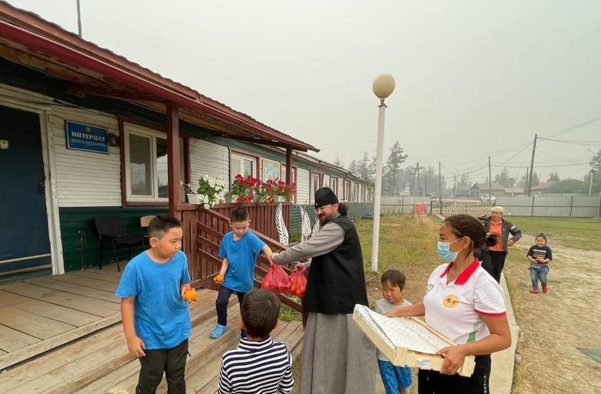 Архиепископ Якутский и Ленский Роман передает фрукты детям из семей, пострадавших от лесных пожаров