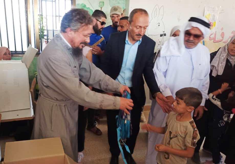 Передача школьных рюкзаков с письменными принадлежностями детям Босры